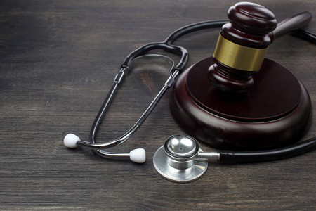 A gavel and a stethoscope placed on a brown table