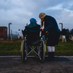 person assisting another in a wheelchair