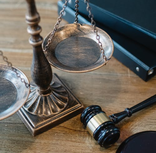 Some scales, a gavel and some legal books on a table